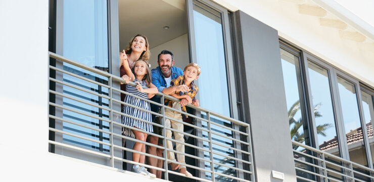 Family waving out of their balcony window
