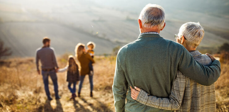 Rear-view of embraced senior couple looking at their family in nature