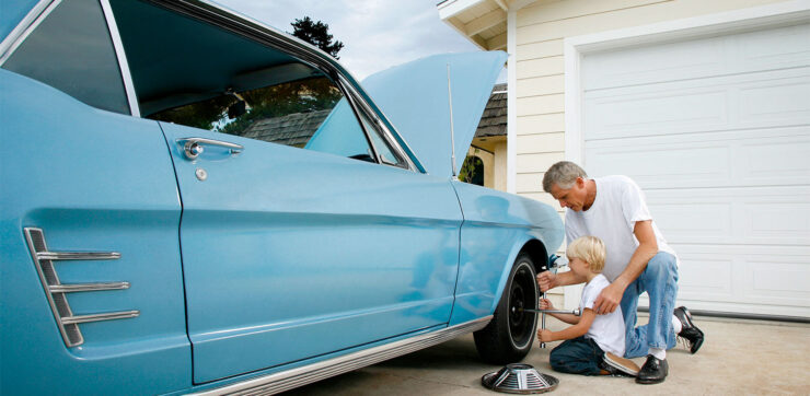 Young boy learning how to change tire with grandpa on classic car